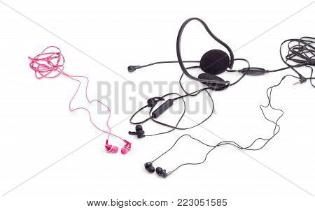 Red and black earphones, black wireless earphones and headset with full size headphones and microphone on a white background