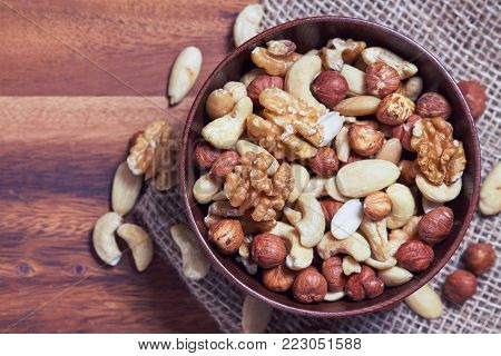 Mixed nuts including hazelnuts, walnuts, blanched almonds and cashews in wooden bowl. Top view with copy space