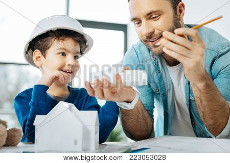 Checking results. Upbeat father and his little son sitting at the table in the office and looking at the results of 3D printing, being the part of a house model