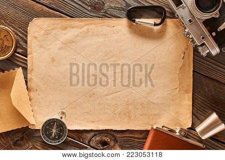 Vintage old 35mm camera on wooden background with old blank paper sheet
