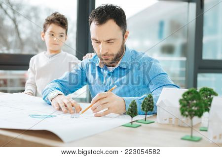 Lack of attention. Bristled young architect working on a blueprint and taking no heed of his little son touching his back and attracting attention