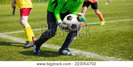 Soccer Goalkeeper Holding Soccer Ball. Soccer Goalkeeper Catching Skills. Youth Football Teams Competing in School Soccer League Tournament