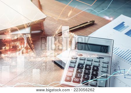 Business or finance background concept.Close up calculator for accounting & finances for economy saving money on  brown office desk.Double exposure offshore oil and gas platform industrial with chart.
