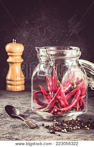 Red hot chilli pepper paprika in glass jar and peppers seed ball and pepper mill on stone table Ingredient for Mexican cooking Trendy toned image in rustic style