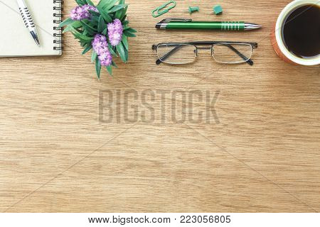 Top view aerial image shot of arrangement accessory business background concept.Flat lay black coffee & essential items pen and notebook with plant in pot on modern wooden table at home office desk.