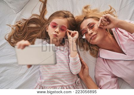 Perfect selfie. Top view of young beautiful mother and her cute daughter taking selfie with smart phone and smiling while lying on the bed at home