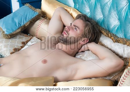 Guy with beard on unshaven face and sexy bare torso, chest lie on bed. Desire, erotic concept. Daydreaming, rest, relax, comfort.