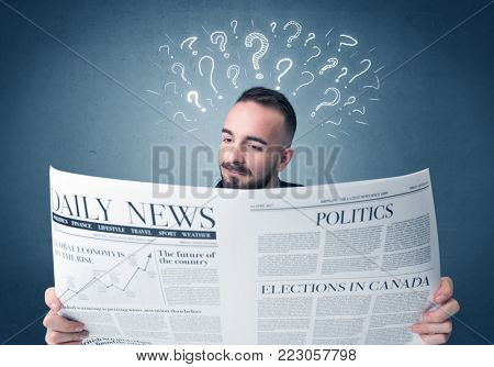 Young confused businessman reading daily newspaper with question marks above his head