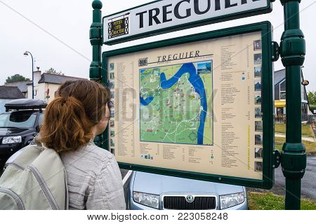 TREGUIER, FRANCE - JULY 2, 2010: tourist looks on outdoor city map in Treguier town. Treguier is port town in the Cotes-d'Armor department in Brittany.