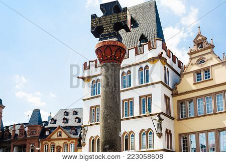 TRIER, GERMANY - JUNE 28, 2010: medieval Marktkreuz (Market Cross) on Hauptmarkt (Main Market square) in Trier city in summer. Alter markt square is central and one of the largest squares in the city