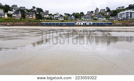 PERROS-GUIREC, FRANCE - JULY 2, 2010: sand beach Plage de Trestrignel and view of Boulevard de Trestrignel in Perros-Guirec town in the Cotes-d'Armor department in Brittany in rainy summer day