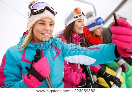 Girl making selfie in ski lift while lifting on ski terrain with friends