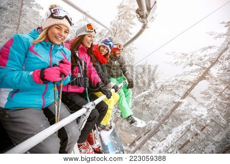 Young happy people in ski lift lifting to ski terrain