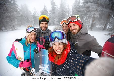 Smiling group of skiers together in mountain