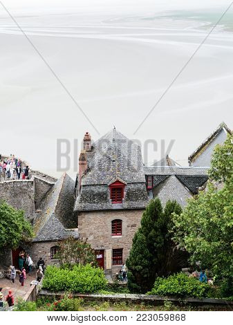 LE MONT SAINT-MICHEL - JULY 5, 2010: above view of visitors inside Saint Michael's Abbey and silted tidal bay in low tide around the castle. Le Mont Saint-Michel is an island commune in Normandy