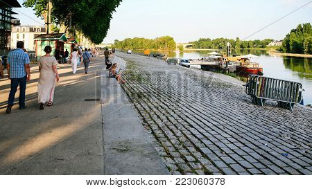 ORLEANS, FRANCE - JULY 9, 2010: people walk along Quai du Chatelet on waterfront of Loire river in Orleans city. Orleans is the capital of the Loiret department and of the Centre-Val de Loire region