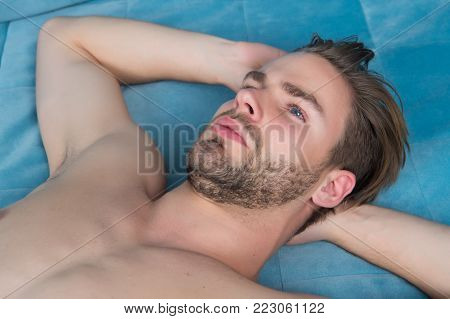 Guy with beard on unshaven face and sexy bare chest lie on blue bed cover. Desire, erotic concept. Daydreaming, rest, relax, comfort.