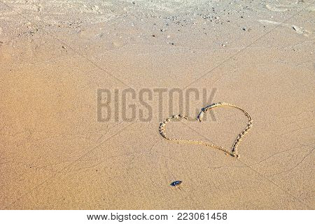 A heart symbol written in the sand on the beach..