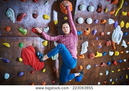 full length portrait of a sporty woman in boulder climbing hall