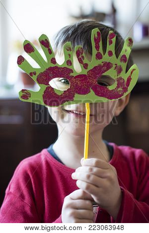 Portrait Of A 6 Year Old Boy With A Carnival Mask Made By Himself At Home