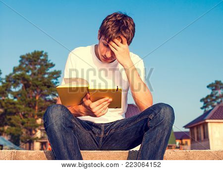 Toned Photo of Sad Young Man read a Book outdoor