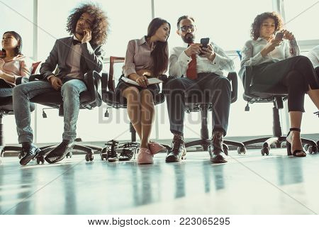 Young team of coworkers sitting on chairs. Everybody is busy with own thoughts.
