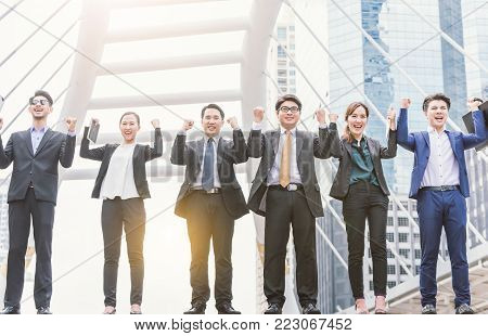 happy Successful business group People Hands Raised successful with city background Successful business group with arms up with city background