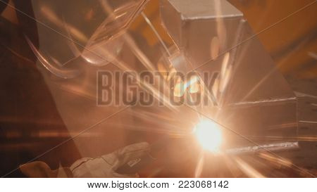 The welder welds metal parts at the plant, industrial plasma welding, modern technology, close-up