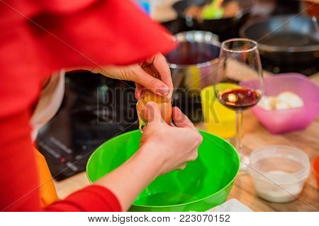 Close up woman's hands adding egg to dough ingredients in green plastic bowl