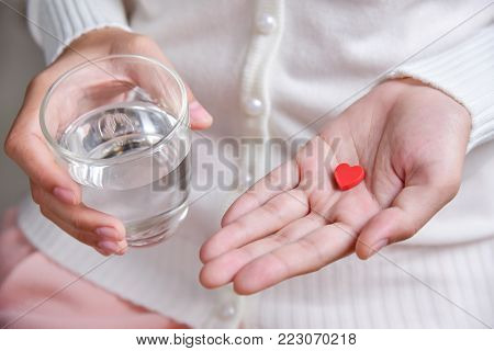 Female hands with white shirt is holding a pill in heart shape and glass of water. Valentines concept. Love. Health. Disease. Illness.