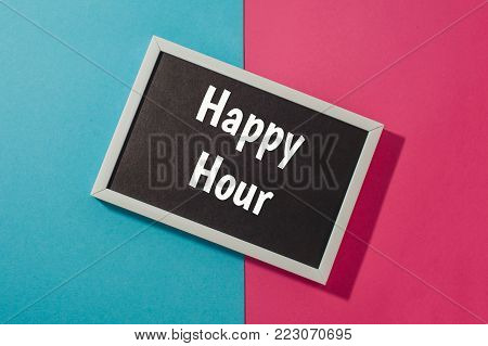 Happy hour - text on chalkboard on blue and pink bright background.