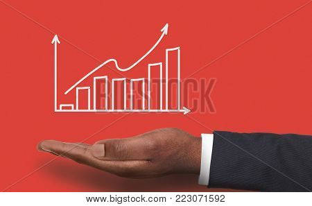Conceptual business success background. African-american male hand over red backdrop with growth graph. Revenue, financial well-being and achievenment concept, copy space