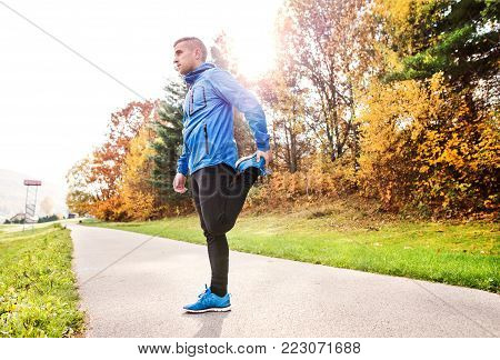 Young runner in blue jacket outside in colorful sunny autumn nature standing on an asphalt path, stretching. Trail runner training for cross country running.