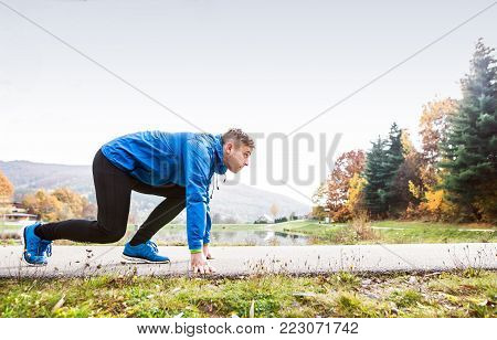 Young runner in blue jacket at the lake on an asphalt path leading through green grass in steady position. Trail runner training for cross country running outside in colorful sunny autumn nature.