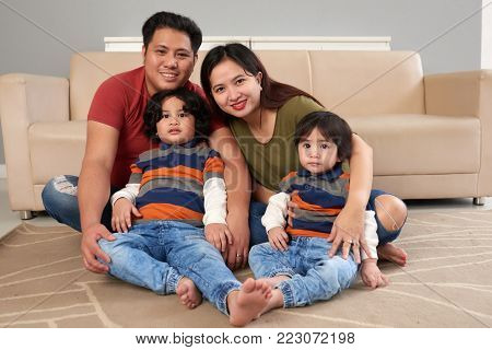 Cheerful Filipino family sitting on the floor in living room