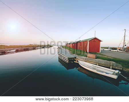 Motorboat for fishing tied to a wooden floating pier. Small port at village, blue bay with calm water.
