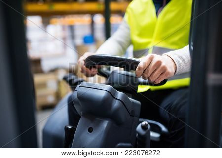 Unrecognizable man forklift driver working in a warehouse.
