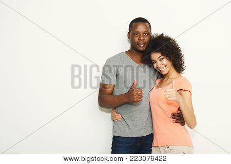 Happy african-american couple in casual embracing and showing thumbs up at white background, studio shot, copy space, isolated