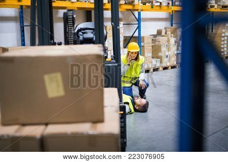 An accident in a warehouse. Woman with smartphone and her colleague lying on the floor next to a forklift.