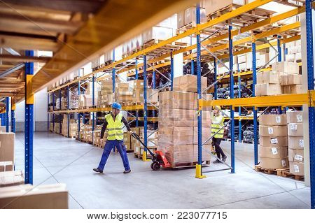 Young warehouse workers pulling a pallet truck with boxes.