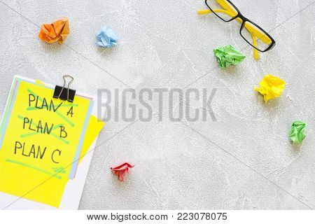 New Idea Creativity Business Concept with a copy space, Plan A, Plan B, PlanC list, glasses and colorful crupmled paper balls on a grey concrete background, flat lay, top view