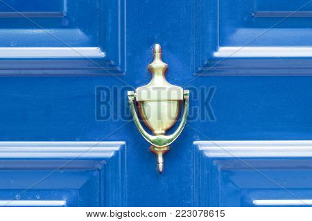 Door knocker. Old antique golden brass knocker on the abstract blue wooden doors for knocking close up