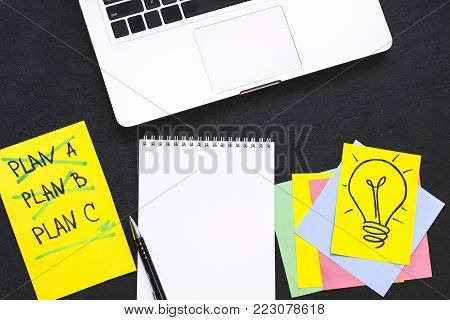 New Idea Creativity Business Concept with a copy space, Laptop, Plan A, Plan B, PlanC list, light bulb image and a blank notepad on a black concrete background, flat lay, top view