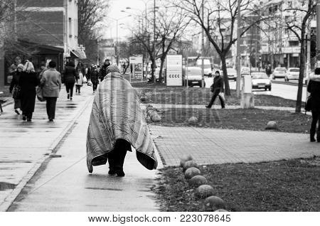 Homelessness. Poor homeless person or refugee covered with blanket walking or wander on the urban street of the city on the cold raining day black and white
