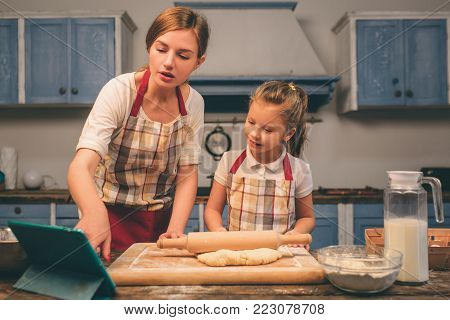 Cooking homemade cakes. Happy loving family are preparing bakery together. Mother and child daughter girl are cooking cookies and having fun in the kitchen. searching for recipes on the tablet.