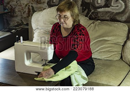 The woman is engaged in needlework at leisure. Sitting on the couch in front of the sewing machine.