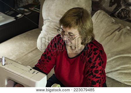 The woman is engaged in needlework at leisure. Sitting on the couch in front of the sewing machine. Closeup.
