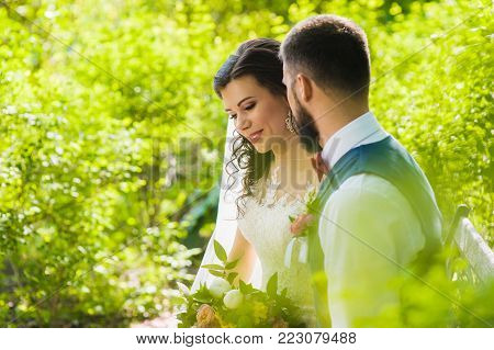 Just married smiling couple in love in the magic shining sunny green garden outdoors