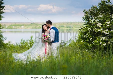 Amazing just married couple in the landcape with water and blossom bushes outroors. River and flowering bush in the background