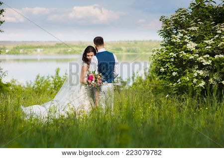 Amazing just married couple in the landcape with water and blossom bushes outroors. river and flowering bush in the background.